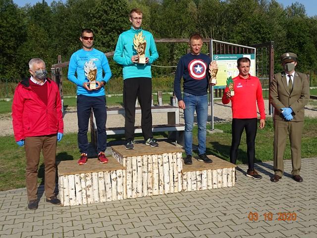 Zwycięzcy w kategorii Open Mężczyzn stoją na drewnianym podium. Z lewej strony towarzyszy im burmistrz.